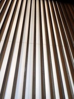 国立新美術館は天井がとても高いため、上からの照明では足下まで届かない。そこで壁面全体が照明になっているのだ。この「光壁」、デザインは日本の行灯(あんどん)をモチーフにしているそうだ