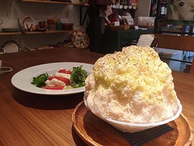 イタリア料理店「ペルラヴィータ十号坂」の一番人気「桃のカルボナーラ」(税込み800円)と、「南イタリア直送チーズ ブッラータのカプレーゼ仕立て」(税込み1700円)。桃のカルボナーラのベースは自家製練乳のかき氷で、それにエキストラバージンオリーブオイル、黒コショウがかかっている。本当に、パスタのカルボナーラのような風味を感じた