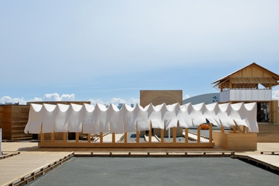 """「冷涼珈琲店-煎」はAGFと建築家・長谷川豪氏による、中央通路にもうけられた""""長い縁側""""。腰掛けてのれんを吹き抜ける風を感じられる。会場には家や住まいに関連するものを中心に幅広い本を集めた「代官山 蔦屋書店」も出店。メーンスペースでは建築家らのトークショーが毎日開催される"""