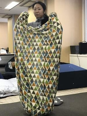 筒状ブランケットの中にあぐらクッションを内蔵した「こもれる毛布付きのあぐらクッション」(5490円)。ネイビー、マルチカラーの2色。立ち上がってもすっぽり体が隠れるサイズだ