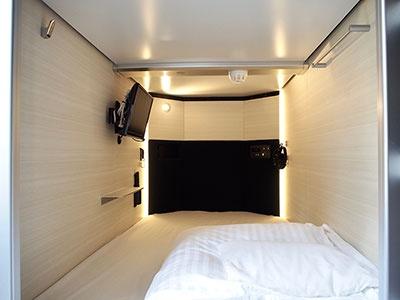 薄型テレビ付きカプセルルーム。室内には折りたたみデスク、時計、鏡、ハンガーも用意