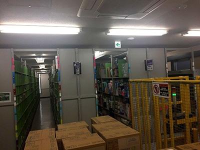 棚が並んでいる様子は、さながら図書館の書庫。この写真の棚は、おむつなどが詰め込まれていた。手前にある箱はミネラルウォーター