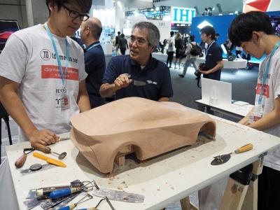 赤い自動車のデザイン画から起こしたクレイモデル。プロのカーモデラーから指導を受けつつ、カーデザインに興味を持つ学生たちが、クレイモデルを仕上げる