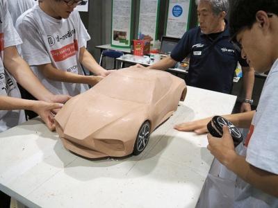 銀色の自動車のデザイン画を見て学生たちが作っているクレイモデル。デザイン画よりもボンネットとフェンダーがそれぞれにきちんと主張するようなアレンジが加わっているようだ。フォーミュラーカーをイメージしているようにも見える