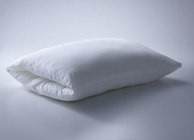 「WHOLLY PILLOW」(9800円)。両側から腕を入れればうつぶせ寝用の枕にもなる。専用の枕カバーを外してひも状にして空洞に通せば、防災頭巾としても使用できる。オーガニックコットン100%の枕カバー付き。クラウドファンディングサイト「Makuake」で販売中。縦50×横70×厚さ約18cm