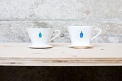 ブルーボトルコーヒーが使用するドリッパー。左が新型、右が従来から使っていたもの。比較すると左は底が円形の平面になっていることが分かる。新型ドリッパーは店舗やオンラインショップで販売もしている。価格は2300円