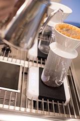 acaia pearlは抽出したコーヒーを受けるカラフェの下に置いて使う。店舗でよく見ると、バリスタはみな使っているはず