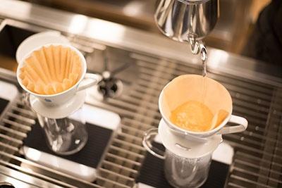 従来のペーパーフィルター(右)は、ドリッパーに設置後に湯通しするが、左の新型は湯通しがいらない。藤岡氏によると「従来のドリッパーで入れたコーヒーもおいしい」のだが、湯通しの手間が省けるのが新型のメリットだ