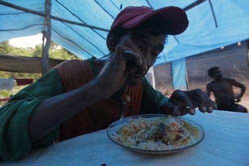 ある日の昼食。1つの皿に米に豆、魚のスープを入れ、ファリーニャ(タロイモの粒を固めたアマゾンの保存食)を振りかけて食べる  (c)Eduard MAKINO