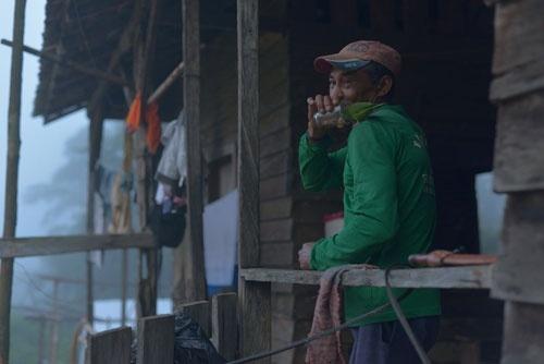 早朝、鉱山に向かう前の慌ただしい時間、ガリンペイロの1人がペットのインコにコーヒーを与えていた (c)Eduard MAKINO