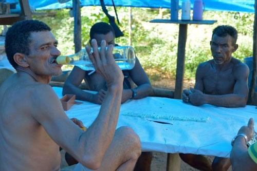 ピンガ(サトウキビの蒸留酒)を回し飲みしながら、賭けドミノで遊ぶガリンペイロたち。話題は金のこと、プータ(娼婦)のこと、クイジネーラのこと…… (c)Eduard MAKINO