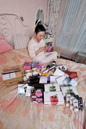 越境ECサイトで購入した日本商品に囲まれるチェン・シーさん(写真:町川 秀人、以下同)