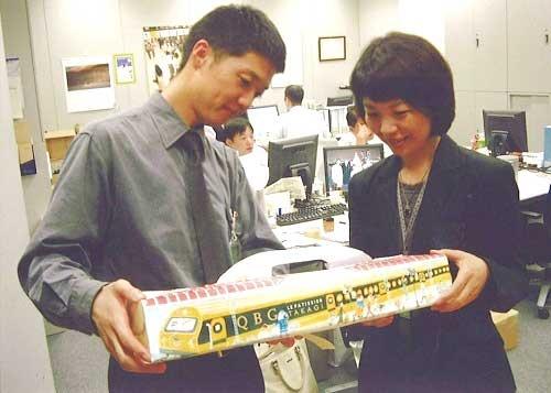 エキュート品川立ち上げを前に、新商品を検討。手にする50センチの電車型ロールケーキは話題を呼んだ