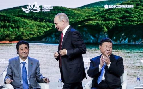 東方経済フォーラムでパネルディスカッションに出席する安倍晋三首相(左)、ロシアのプーチン大統領(中央)、中国の習近平国家主席(右)(写真:代表撮影/ロイター/アフロ)
