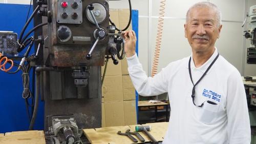 ケン・マツウラレーシングサービス創業者、現顧問の松浦賢氏。後ろは創業期に初めて「中古で買った」工作機械。