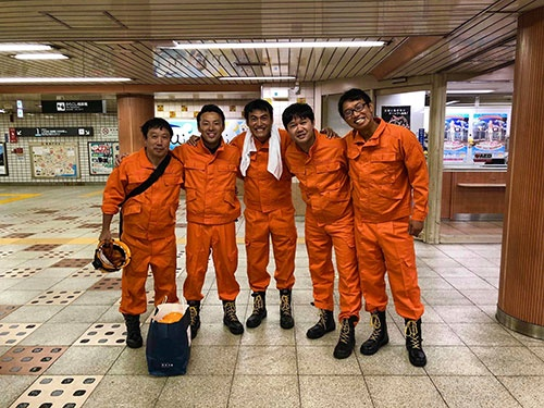 東急電鉄、夜の三軒茶屋駅に、揃いの「オレンジ色のつなぎ」で集合しました