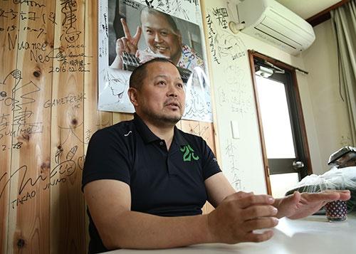 個人商店の光山英明社長。運営する肉料理専門店「肉山」の壁には、来店した有名人のサインがすき間なく並ぶ(写真:陶山勉、以下同)