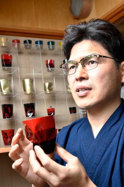 漆だけで作る器「thin」を手に持つ武藤さん。型のコップを潰すことで、独自の形状を実現する(写真:早川俊昭)