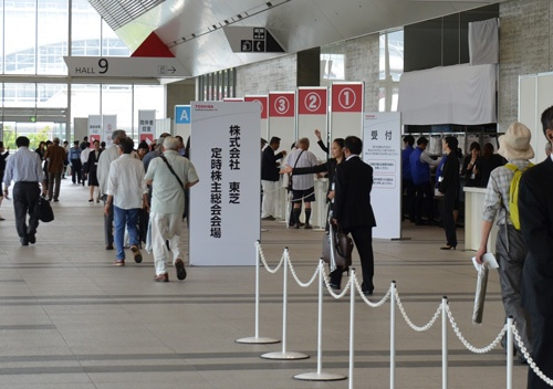 千葉県の幕張メッセで開かれた東芝の株主総会。スタッフが金属探知機を使って安全確認をしていた