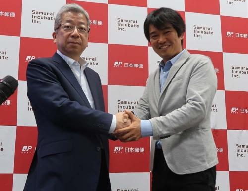 笑顔で握手する横山・日本郵便社長と榊原・サムライインキュベート社長