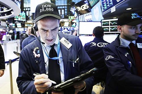 1月4日、米株式市場でダウ工業株30種平均が初めて2万5000ドルの大台を突破、活況に沸いた。トレーダーの男性が「ダウ 25,000」という文字の入った記念の帽子をかぶっている。(写真:ユニフォトプレス)