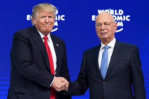 ダボス会議を運営する世界経済フォーラムのクラウス・シュワブ会長(右)と握手をするドナルド・トランプ米大統領。(写真:AP/アフロ)