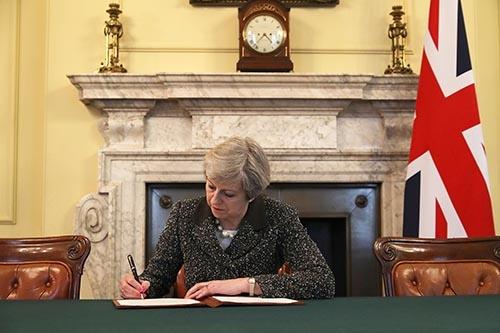 3月29日、英国のメイ首相はEU基本条約(リスボン条約)50条を発動し、EUに対して離脱を正式に通知した。EU離脱を正式通告する書簡に署名するメイ首相 (写真:PA Photos/amanaimages)
