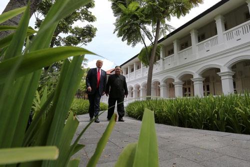 6月12日、昼食前に並んで散策するドナルド・トランプ米大統領と北朝鮮の金大恩委員長(写真:ロイターアフロ)