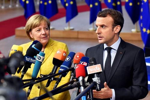 ドイツのメルケル首相(左)とフランスのマクロン大統領は、ベルギーのブリュッセルで開かれたEU首脳会議において14日、共同記者会見を行った。(写真:ロイター/アフロ)