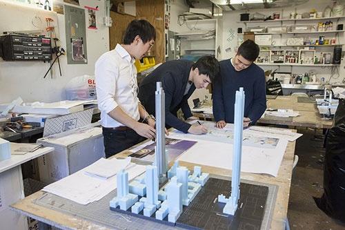 立体模型と平面図を照らし合わせ、模型室でプロジェクトの進捗確認をするスタッフも