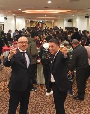 社員の家族とともに新年を祝う社長の李宏道(左)と、専務の李宏為(右)
