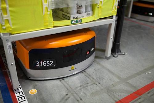 棚を動かしているのはオレンジと黒の小さなロボットだ。約340キロの重さまで背負うことができる。全世界で10万台が稼働しているという