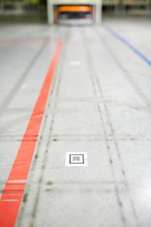 ロボットは床にあるQRコードで自分の位置を把握している。棚自体が動くようになったことで、数時間かかっていた作業が数分になった