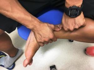 両手の親指を下腿三頭筋(ふくらはぎ)に当て、膝に向けて押し上げてマッサージしていく。