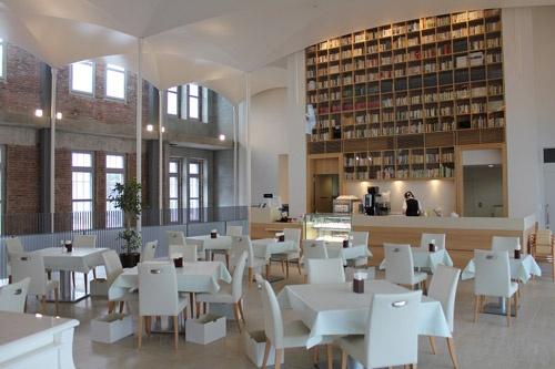 """<span class=""""fontBold"""">2階のカフェ。東西は書棚の壁。上部には、直径100㎜の細い柱でクロスボールト状の白い天井を浮かせた</span>(写真:日経アーキテクチュア)"""