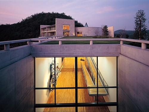 「ベネッセハウスミュージアム」の本館を南側から見る。ガラスの開口の内部がギャラリーで、50×8mの平面を持つ吹き抜け空間が地下に埋められている(写真:三島叡)