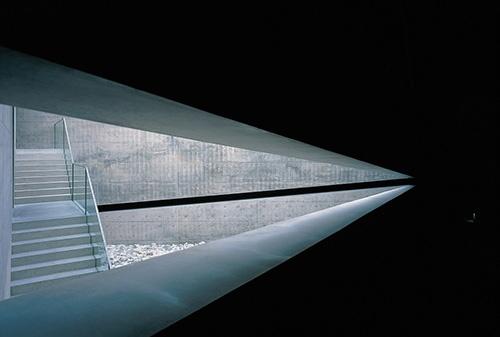 直島・地中美術館の三角コート。3人の作家の展示スペースを結び付ける。2辺の壁の内側に洞くつのようなスロープが巡る(写真:的野弘路)