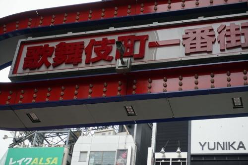 新宿・歌舞伎町の入り口に立つ看板。中央に防犯カメラが見える