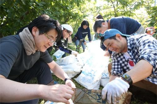 イベント参加者と一緒に農作業をする農園主の金丸直明氏(右、写真=陶山 勉)