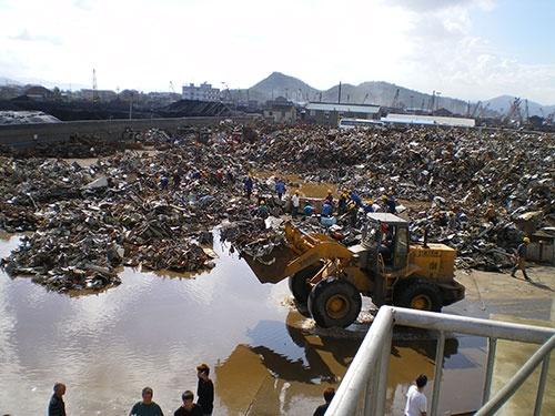 中国・浙江省にある金属スクラップ処理現場の様子。地面に直に置かれた金属ゴミを作業員が手選別している (写真:大橋信胤)