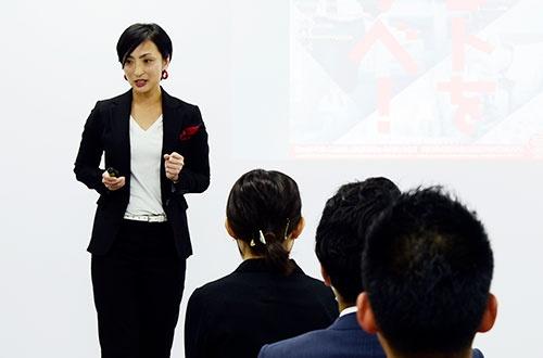 電巧社総務の八木橋幹子さん。黒いスーツにインナーは白、赤のポケットチーフが目を引く。会社全体の紹介を担当した