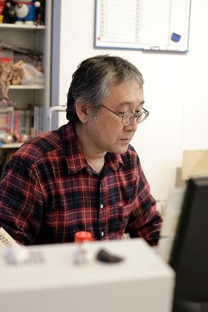田中さんは1962年生まれ。近畿大学在学中に漫画家デビューし、卒業後は玩具メーカーのタカラ(現・タカラトミー)勤務を振り出しに30年以上、会社員兼業の漫画家を続けてきた。現在は京都精華大学マンガ学部で教壇にも立つ。写真は勤務先の大学のデスクで