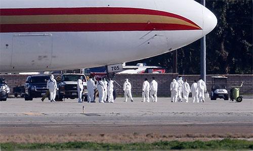 2020年1月29日、米国人195人を乗せた米政府チャーター機がカリフォルニア州南部の米軍基地に着陸した。防護服に身を包んだ医療チームが搭乗者たちを出迎えた(写真:AP/アフロ)