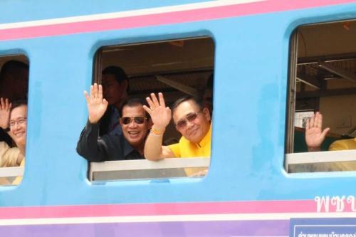 タイからカンボジアに向かう国際鉄道に乗るカンボジアのフン・セン首相(写真左)とタイのプラユット暫定首相