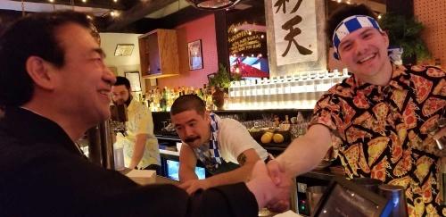 バーテンダーと握手する三和酒類の下田雅彦社長(2019年3月、米ニューヨーク)