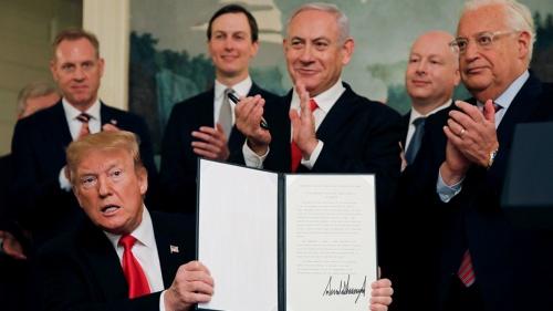 ゴラン高原に関するイスラエルの主権を承認する文書に署名するトランプ大統領(左)。中央に立つのはイスラエルのネタニヤフ首相。その左後方はトランプ大統領の娘婿のクシュナー氏。政権の中東外交のカギを握る親イスラエル派(写真:ロイター/アフロ)