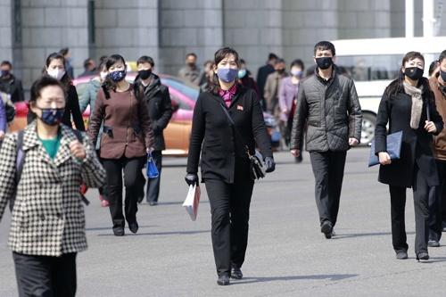 感染防止のためマスクを着用して歩く平壌の人々(写真:AP/アフロ)