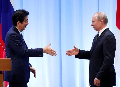 笑顔で握手を求めるのは安倍首相だけ?(写真:代表撮影/ロイター/アフロ)