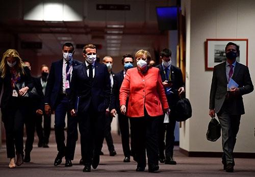 EU首脳会議を終え記者会見に向かうメルケル独首相(右)とマクロン仏大統領(左)(写真:代表撮影/ロイター/アフロ)