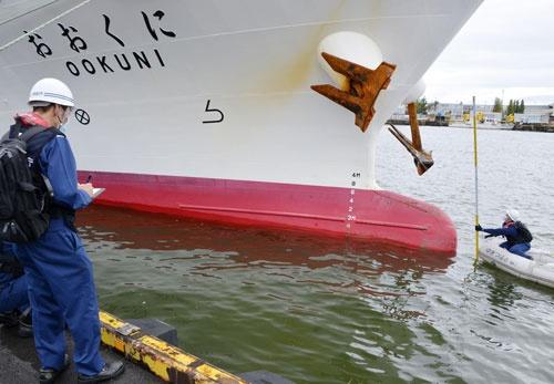 漁業取締船「おおくに」船首下部の突起部分付近を調べる第9管区海上保安本部の職員(共同通信)
